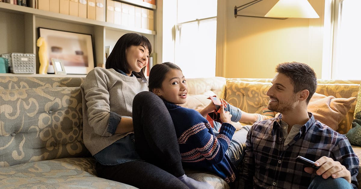 An image of a family relaxing on a couch using a laptop PC.